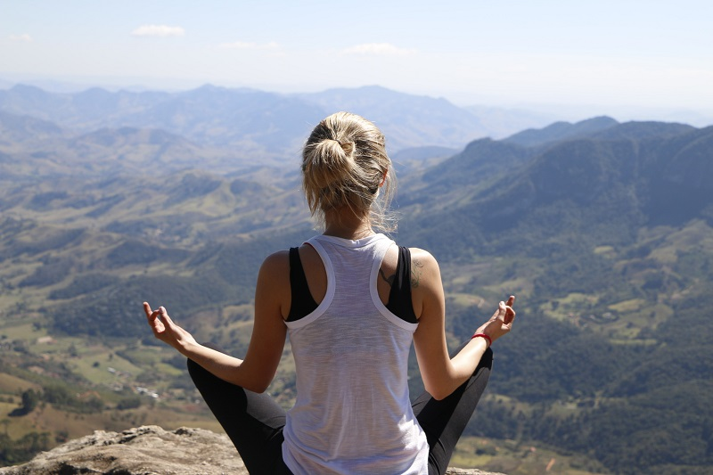 young woman meditating on the mountain top